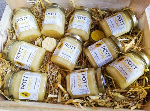 Honiggläser auf Stroh in einer Kiste