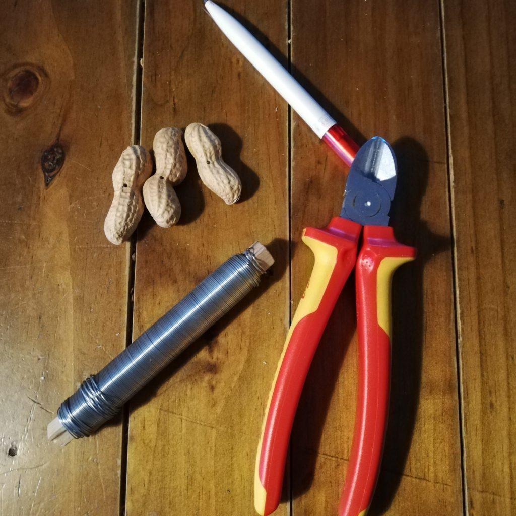 Die Materielen die du brauchst um eine Erdnusskette zum Vogelfüttern zu bauen. Einen Kugelschreiber (oder etwas ähnliches), Draht, einen Seitenschneider und natürlich Erdnüsse.
